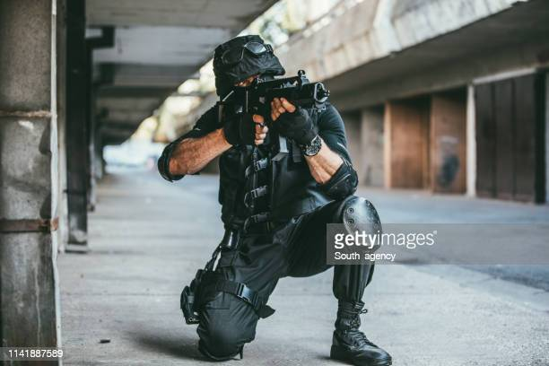 armed soldier aiming a rifle on the street - terrorism stock pictures, royalty-free photos & images