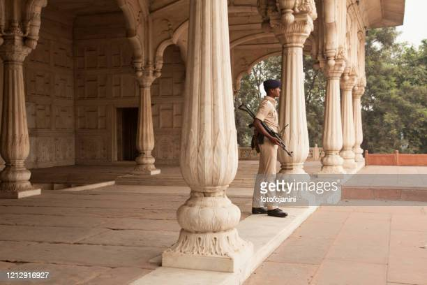 armed soldier out of palace of  red fort delhi - fotofojanini foto e immagini stock