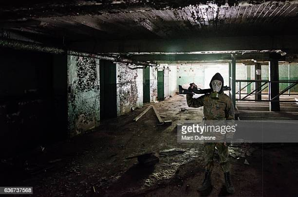 Armed soldier with gas mask standing in abandoned basement