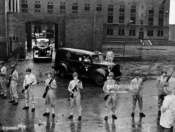 Armed soldiers guard the ambulances that are carrying the bodies of six executed Nazi saboteurs who plotted against the United States away from...