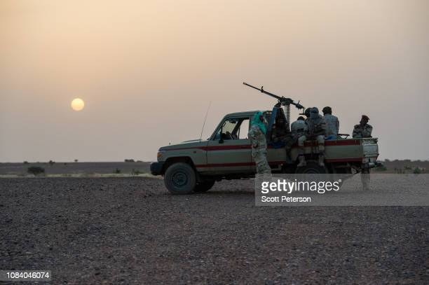 Armed soldiers of the Niger National Guard on duty at sunset as they protect a convoy crossing the Sahara Desert from Niger north to Libya, often...