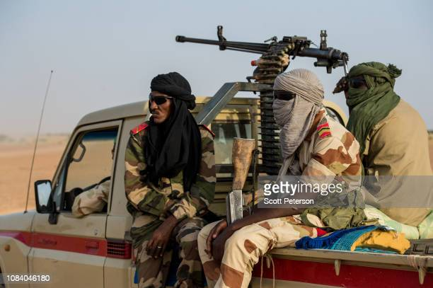 Armed soldiers of the Niger National Guard protect a convoy crossing the Sahara Desert from Niger north to Libya, often with Nigerien workers on...