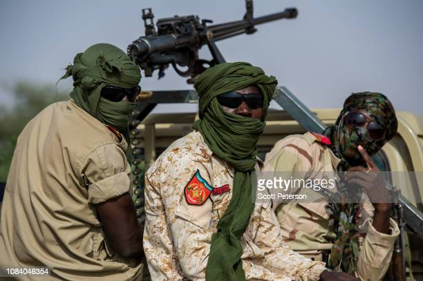 Armed soldiers of the Niger National Guard their heads wrapped in turbans protect a convoy crossing the Sahara Desert from Niger north to Libya often...