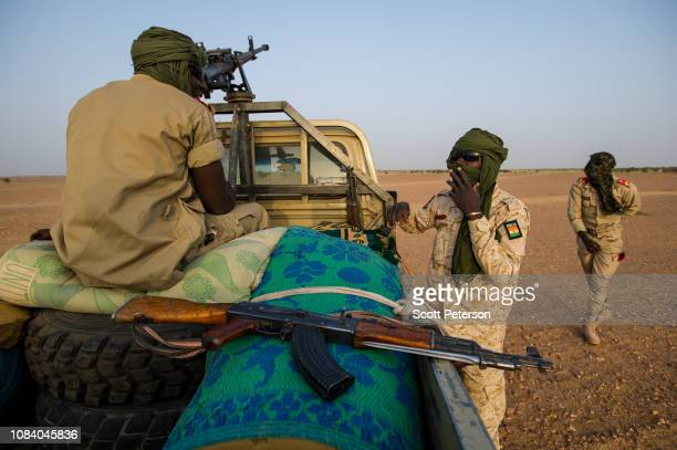 Armed soldiers of the Niger National Guard wearing turbans against heat and dust protect a convoy crossing the Sahara Desert from Niger north to...