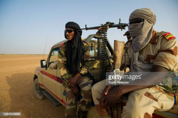 Armed soldiers of the Niger National Guard, wearing turbans against heat and dust, protect a convoy crossing the Sahara Desert from Niger north to...