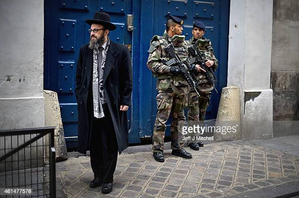 Armed soldiers patrol outside a School in the Jewish quarter of the Marais district on January 13 2015 in Paris France Thousands of troops and police...