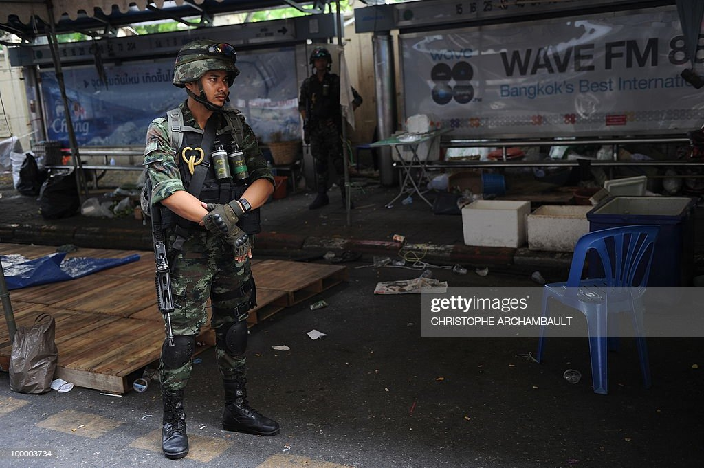 Armed soldiers stand guard at the abandoned shelters within an anti-government protest site a day after an assault, in downtown Bangkok on May 20, 2010. Thai authorities on imposed a curfew for three more nights in Bangkok and 23 other provinces to quell conflict in the aftermath of an army offensive against anti-government protesters. AFP PHOTO/Christophe ARCHAMBAULT