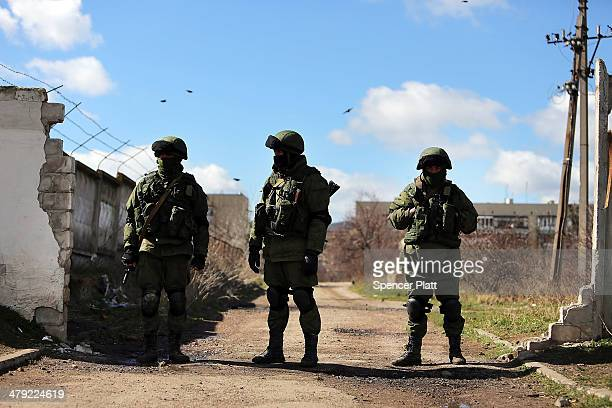 Armed soldiers without identifying insignia keep guard outside of a Ukrainian military base in the town of Perevevalne near the Crimean city of...