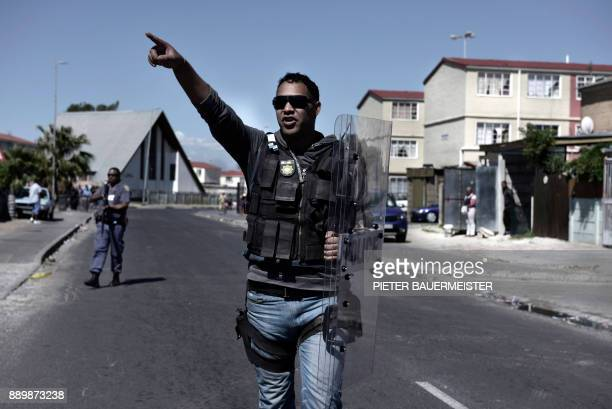 Armed South African police officer patrol in a street as they respond to a shooting of two alleged gang members in Manenberg Cape Town on October 18...