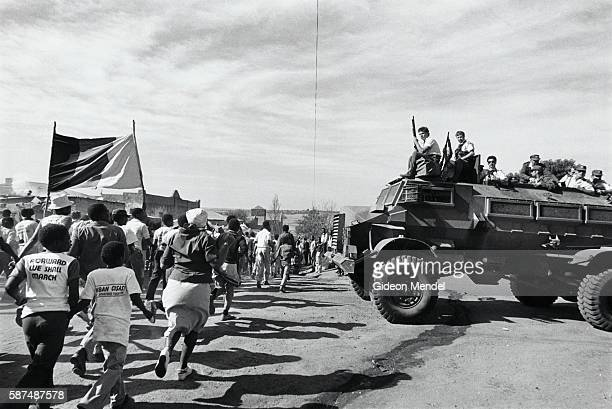 Armed South African police on an armored Casspir vehicle watch the procession of mourners carrying the banned African National Congress flag at the...