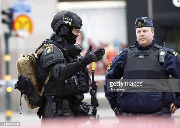 Armed Swedish police officers close off a city street near to the Ahlens department store in Stockholm Sweden on Friday April 7 2017 A hijacked truck...