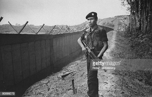 Armed Thai soldier standing guard next to gray 12fthigh concrete wall that runs 15 miles through the mountains jungles along the ThailandMalaysian...