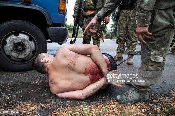 Armed Ukrainian forces detain a proRussian militant in the village of Chornukhine in the Lugansk region on August 18 2014 A Ukrainian warplane was...