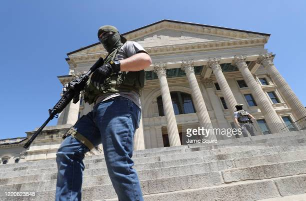 Armed veterans demonstrate in front of the state capitol building demanding that businesses be allowed to open up, people allowed to work, and lives...