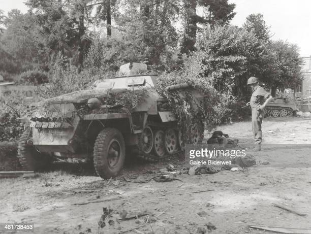 A GI armed with a M3 Grease gun looks at the corpse of a German soldier behind a German halftrack camouflaged with branches 12th August 1944 It...