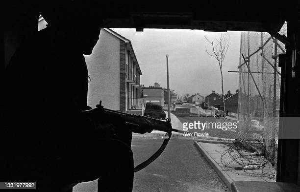 Armed with a SLR rifle a British soldier peers out from the rear of an FV603 Saracen armoured personnel carrier at the start of a mobile patrol...