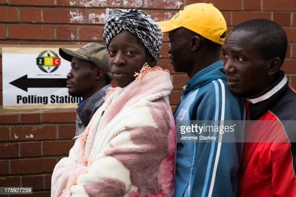 Armed with flasks of hot tea and blankets to ward off the pre-dawn cold, dozens of Zimbabwean voters queued outside the polling stations in Harare...