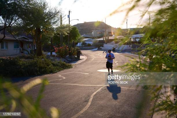 Armed with pro-Biden leaflets, masks, visors and good shoes, Democratic Party supporter Miguel Vargas canvasses the suburbs of Phoenix, Arizona,...