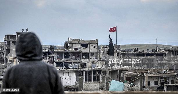Armed women take routine security measures near the wreckages left by fighting in the center of the Syrian town of Kobani on February 18, 2015 after...