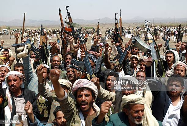Armed Yemeni men loyal to the Shiite Huthi movement shout slogans during a tribal gathering against alQaeda militants in the Bani alHarith area on...