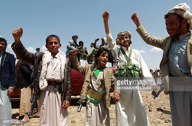 Armed Yemeni men loyal to the Shiite Huthi movement shout slogans during a tribal gathering against alQaeda militants in the Bani alHarith area north...