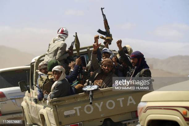 TOPSHOT Armed Yemeni men raise their weapons as they gather near the capital Sanaa to show their support to the Shiite Huthi movement against the...