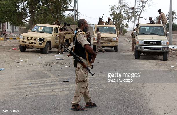 Armed Yemeni men stand next to the entrance of an army headquarters near Aden airport after Yemeni government forces supported by a Saudiled...