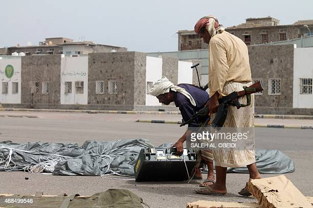 Armed Yemeni supporters of the separatist Southern Movement inspect a box attached to a parachute reportedly airdropped by the Saudiled coalition at...