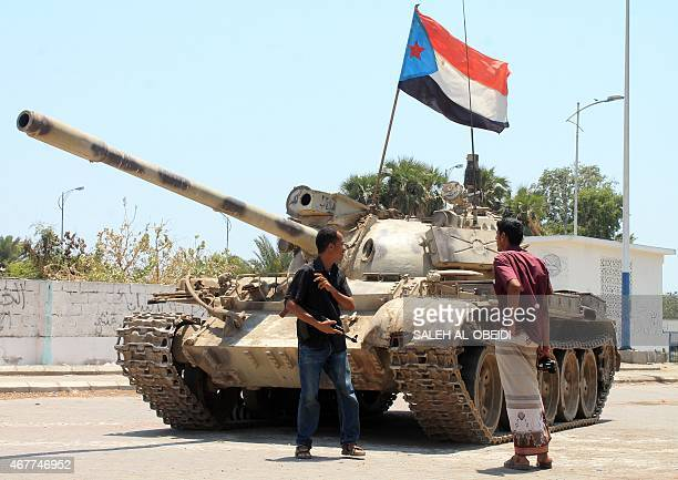 Armed Yemeni supporters of the southern seperatist movement stand next to a tank bearing the movement's flag which they confiscated from a military...