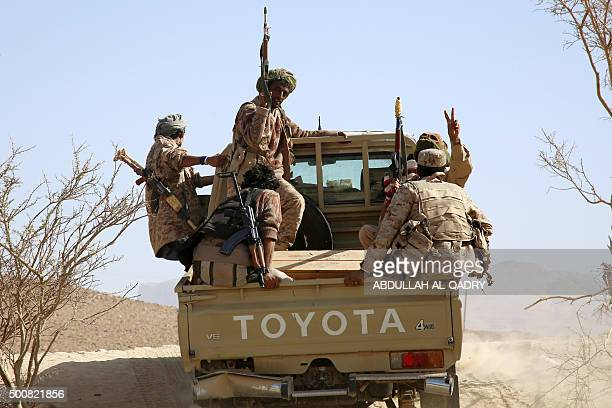 Armed Yemeni tribesmen from the Popular Resistance Committees supporting forces loyal to Yemen's Saudibacked President Abedrabbo Mansour Hadi raise...