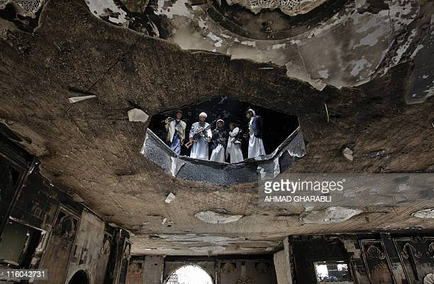 Armed Yemeni tribesmen loyal to dissident tribal leader Sheikh Sadiq al-Ahmar inspect damage at his house in Sanaa on June 7, 2011 while...