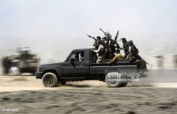 TOPSHOT Armed Yemeni tribesmen loyal to the Shiite Huthi rebels sit in the back of an armed vehicle during a gathering to mobilise more fighters into...