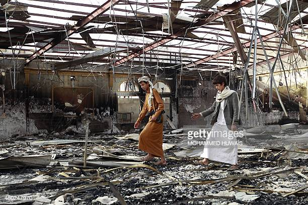 Armed Yemenis walk on the debris at a wedding hall which was reportedly hit by a Saudiled coalition air strike in the capital Sanaa on July 10 a few...