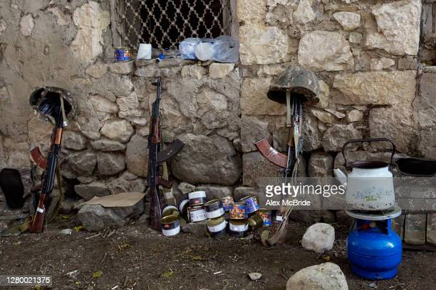 Armenian AK-47s rest against a wall in a makeshift camp while soldiers rest in an undisclosed area of Nagorno-Karabakh on October 13, 2020. Russia...