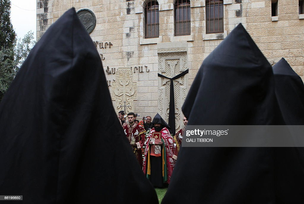 Armenian clergy take part in a prayer at a monument next to St