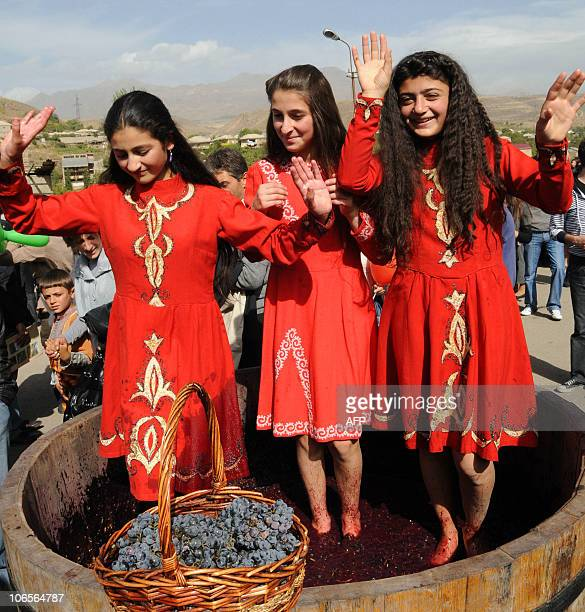 Armenian girls dance while treading grapes with bare feet during a wine festival in the village of Areni some 100 km of the capital Yerevan on...