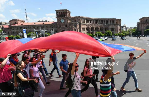 Armenian opposition supporters carrying a giant flag demonstrate in downtown Yerevan on April 26 2018