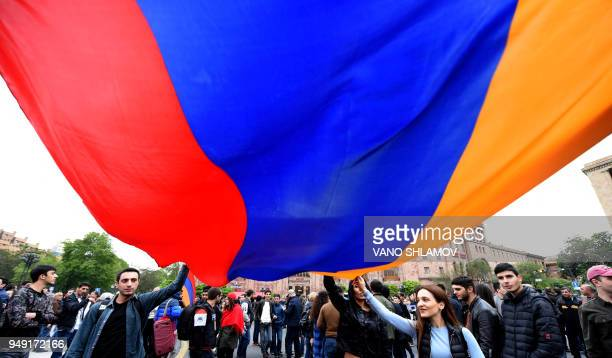 Armenian opposition supporters wave the national flag during a demonstration against the former president's election as prime minister that saw...