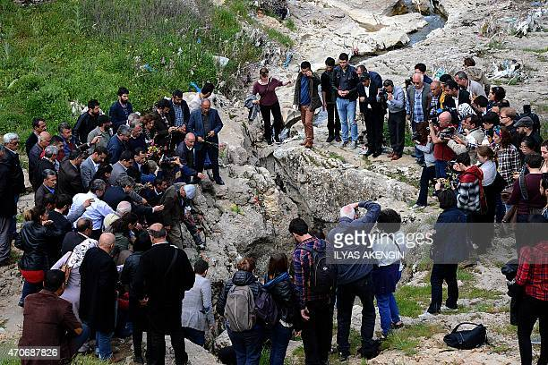 Armenian people gather around a chasm in the mountain during a commemoration ceremony at a site called 'Dudan' near Diyarbakir and believed to be a...