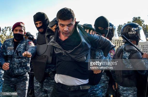 Armenian police officers detain a protestor during a rally against the country's agreement to end fighting with Azerbaijan over the disputed...