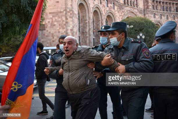 TOPSHOT Armenian police officers detain a protestor near the Government building after a protest against the country's agreement to end fighting with...