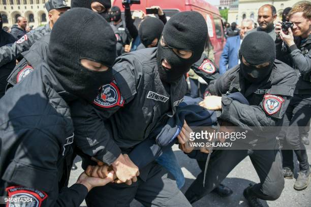 TOPSHOT Armenian policemen detain an opposition supporter during a rally in central Yerevan on April 22 held to protest former president's election...