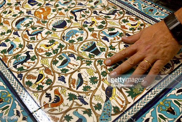 Armenian pottery expert Nshan Balian runs his hand over his ceremic tile replica of the ancient Bird Mosaic from the Armenian chapel near the...