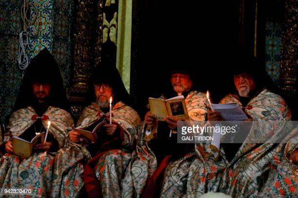 TOPSHOT Armenian priests hold candles as they pray at the Armenian Saint James Cathedral in Jerusalem's Old City on April 5 ahead of the traditional...