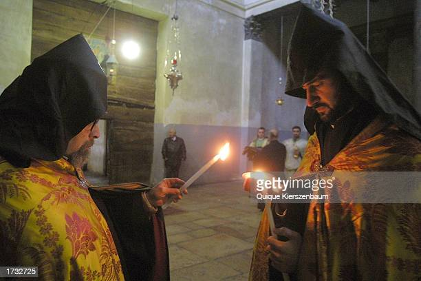 Armenian priests light candles as they make the last preparations before the noon service in the Church of the Nativity January 18 2003 in the West...