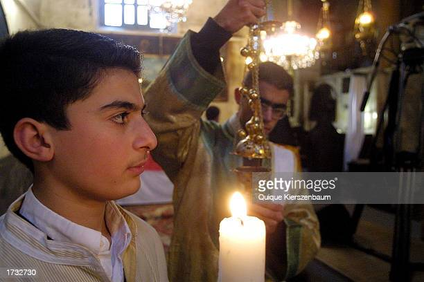 Armenian priests make the last preparations before the noon service in the Church of the Nativity January 18 2003 in the West Bank town of Bethlehem...