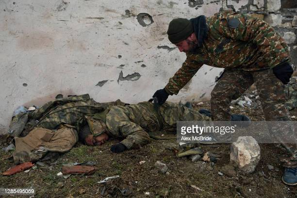 Armenian servicemen collect the bodies of soldiers who had been killed fighting for Azerbaijan on the road where the final days of battle had...