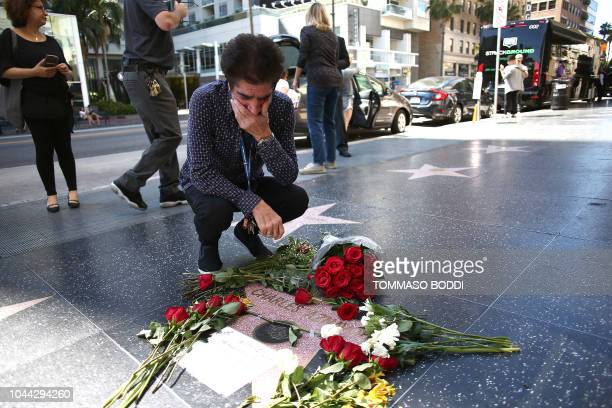 Armenian singer Harout Pamboukjian reacts near flowers placed on musician Charles Aznavour's Star on The Hollywood Walk of Fame on October 01 2018 in...