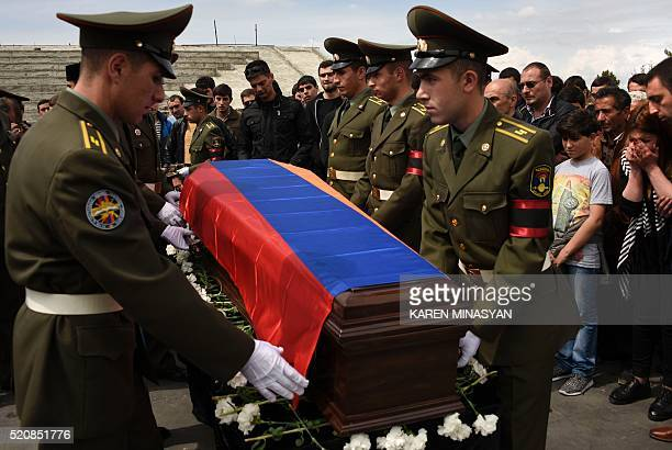 Armenian soldiers carry the flagdraped coffin of one of their comrades killed in NagornyKarabakh during the soldier's funeral ceremony at the...