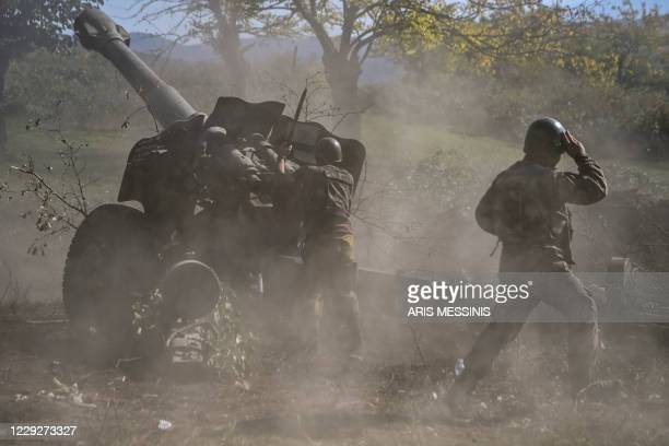 Armenian soldiers fire artillery on the front line on October 25 during the ongoing fighting between Armenian and Azerbaijani forces over the...